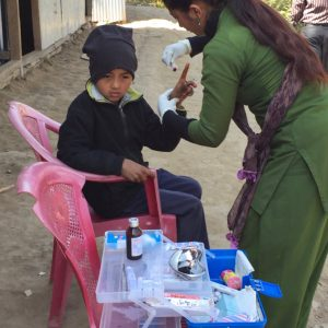 Teacher uses ETC-provided first aid supplies to help boy with injured finger